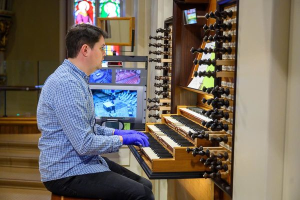Person Playing The Organ While Wearing Gloves For A Live Streamed Mass
